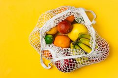 Organic fruits variety in cotton mesh reusable shopping bag - recycling, sustainable lifestyle, zero waste, no plastic. Organic fruits variety in cotton mesh royalty free stock images