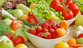 Organic fruits and vegetables. Fresh organic fruits and vegetables on a table royalty free stock photography