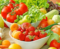 Organic fruits and vegetables in bowls. Fresh organic fruits and vegetables in bowls on a table royalty free stock photos