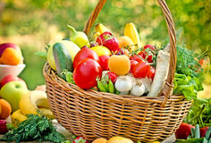 Organic fruits and vegetables in wicker basket. Wicker basket is full with fresh organic fruits and vegetables Royalty Free Stock Photo