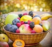 Organic fruits in wicker basket. Fresh organic fruits in wicker baskets on table Royalty Free Stock Photo