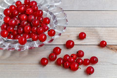 Organic garden berries on old wood table, from above. red currant. crystal vase in the shape of heart. Royalty Free Stock Photo