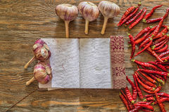 Organic garlic with notebook and hot peppers on old wooden table Royalty Free Stock Image