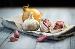 Organic garlic and onion on wooden background. Organic garlic and onion on grey wooden background Royalty Free Stock Photo