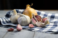 Organic garlic and onion on wooden background. Organic garlic and onion on the textile and wooden background Royalty Free Stock Photos