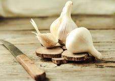 Organic garlic on a wooden rustic background, warm calm gamma. Royalty Free Stock Photos