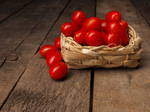 Organic grape tomatoes on a wooden table. Fresh organic grape tomatoes on a rustic wooden table with space for text Royalty Free Stock Photo