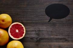 Organic grapefruits and speech bubble Royalty Free Stock Photos