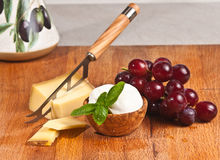 Organic grapes and cheeses for a wine tasting event. Organic red grapes and a cheese knife in gruyere cheese and a wood bowl of mozzarella cheeses with a sprig Stock Images