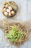 Organic grapes and eggs. On a straw bedding in the wicker plates with wooden and sackcloth background Royalty Free Stock Photos