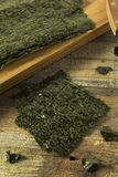 Organic Green Dry Roasted Seaweed Sheets. On a Board Royalty Free Stock Photo