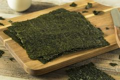Organic Green Dry Roasted Seaweed Sheets. On a Board Stock Photo
