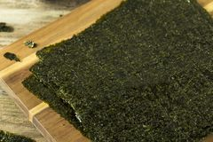 Organic Green Dry Roasted Seaweed Sheets. On a Board Royalty Free Stock Images
