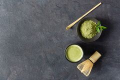Organic green matcha tea. Matcha powder and matcha tea in a bowl. Chashaku spoon and chasen bamboo whisk for brewing matcha tea