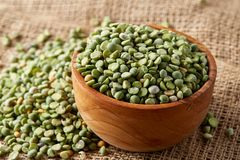 Organic green peas in a bowl on burlap tablecloth, close-up, top view, selective focus, shallow depth of field. Organic green peas in a bowl and some beans on Stock Images