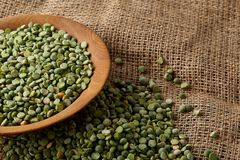 Organic green peas in a bowl on burlap tablecloth, close-up, top view, selective focus. Organic green peas in a bowl and some beans on burlap tablecloth, close Royalty Free Stock Photo