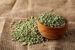 Organic green peas in a bowl on burlap tablecloth, close-up, top view, selective focus. Organic green peas in a bowl and some beans on burlap tablecloth, close Royalty Free Stock Photos