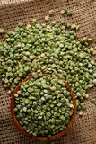 Organic green peas in a bowl on burlap tablecloth, close-up, top view, selective focus. Organic green peas in a bowl and some beans on burlap tablecloth, close Stock Images