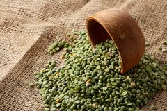 Organic green peas in a bowl on burlap tablecloth, close-up, top view, selective focus. Organic green peas in a bowl and some beans on burlap tablecloth, close Royalty Free Stock Photography
