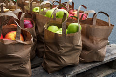 Organic green and red apples in brown paper bags for sale on the Stock Photos