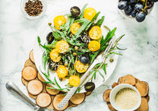 Organic green salad with arugula, yellow tomatoes, olives, sesam Stock Photo