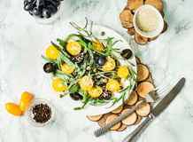 Organic green salad with arugula, yellow tomatoes, olives, sesam. Organic green salad with arugula, yellow tomatoes, olives, grapes and sesame,healthy lifestyle Royalty Free Stock Photography