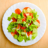Organic Green Salad. Green salad with tomatoes in the wood background Stock Photography