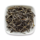 Organic Green Tea (Camellia sinensis) dried long leaves in white ceramic bowl. Stock Images