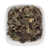 Organic Green Tea (Camellia sinensis) dried whole leaves in white ceramic bowl. Stock Photos