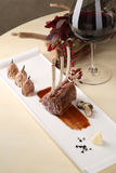 Organic Grilled Lamb Chops with Garlic and sauce on a white plate the background of glass red wine, flowers stock photography