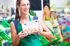 Organic grocery shop clerk offering eggs Royalty Free Stock Photos