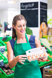 Organic grocery shop clerk offering eggs Royalty Free Stock Images