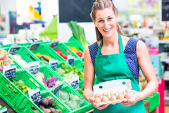 Organic grocery shop clerk offering eggs Stock Images