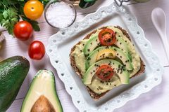 Organic Guacamole Avocado Spread and Slices with Fresh Cherry Tomato and Black Sesame. Healthy Diet Breakfast Concept. Organic Green Guacamole Avocado Spread royalty free stock photo