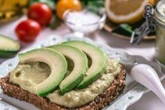 Organic Guacamole Avocado Spread and Slices with Fresh Cherry Tomato and Black Sesame. Healthy Diet Breakfast Concept. Organic Green Guacamole Avocado Spread royalty free stock image