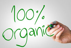 100% Organic hand writing with a green mark on a transparent board.  royalty free stock image