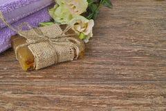 Organic handmade soap, purple sauna towel and flowers Stock Image
