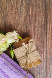 Organic handmade soap, purple sauna towel and flowers on walnut tree background, layout with free text space Royalty Free Stock Photo