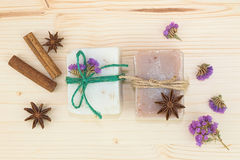 Organic handmade soaps decoration by spices cinnamon, star anise and dry flowers on wood board Stock Photos