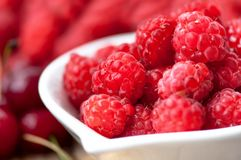 Organic and healthy raspberry in white bowl. With wild berries on background Royalty Free Stock Photography