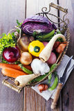 Organic healthy vegetables in the rustic basket. Colorful organic healthy vegetables in vintage metal basket on rustic wooden background Stock Photos