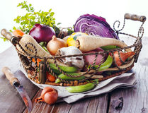 Organic healthy vegetables in the rustic basket. Colorful organic healthy vegetables in vintage metal basket on rustic wooden background Royalty Free Stock Images