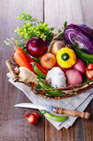 Organic healthy vegetables in the rustic basket. Colorful organic healthy vegetables in vintage metal basket on rustic wooden background Stock Photography