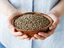 Organic Hemp Seeds. A woman holding a wooden bowl of hemp seeds Stock Image