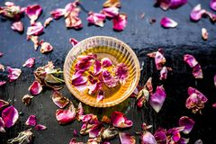 Organic and herbal face pack of Honey & Gram flour with its thick liquid mixture and some rose petals for good aroma on wooden sur. Face used to cure acne & stock photography