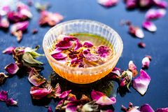Organic and herbal face pack of Honey & Gram flour with its thick liquid mixture and some rose petals for good aroma on wooden sur. Face used to cure acne & royalty free stock photo