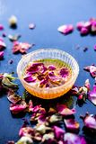 Organic and herbal face pack of Honey & Gram flour with its thick liquid mixture and some rose petals for good aroma on wooden sur. Face used to cure acne & royalty free stock image