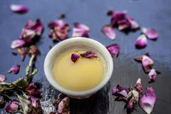 Organic and herbal face pack of Honey & Gram flour with its thick liquid mixture and some rose petals for good aroma on wooden sur. Face used to cure acne & royalty free stock images