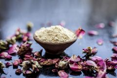 Organic and herbal face pack of Honey & Gram flour with its thick liquid mixture and some rose petals for good aroma on wooden sur. Face used to cure acne & stock photo