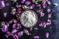 Organic and herbal face pack of Honey & Gram flour with its thick liquid mixture and some rose petals for good aroma on wooden sur. Face used to cure acne & stock image